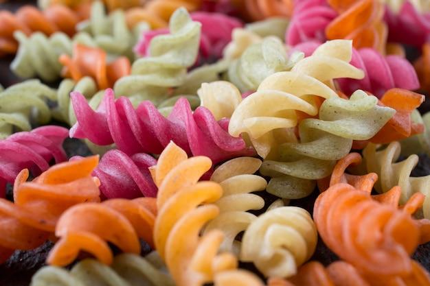 Конец-вверх ярких покрашенных макаронных изделий итальянского fusilli сухих от овощей.