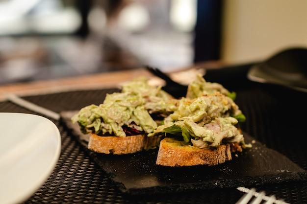 Фьюжн кухня подается в ресторане, испанский пинчо с салатом, соусом карри и курицей