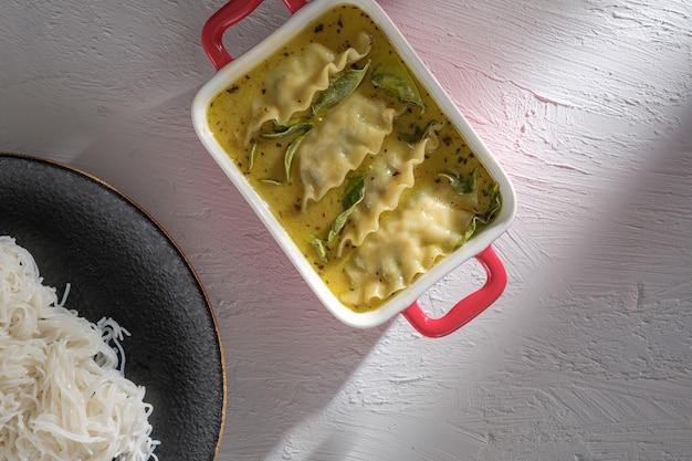 グリーンカレーと餃子のフュージョン料理。蒸し米やビーフンにタイ料理を添えたグリーンカレー(kaeng kheiyw hwan)。とても人気のあるタイ料理、餃子スープ。