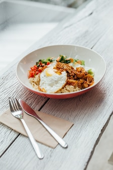 Fusion food rice bowl toppings kimchi pork, organic fried egg, korean eggplant and salad.