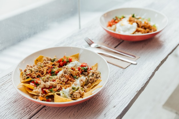 Fusion food soboro chicken nachos: japanese-style stir-fried chicken with tomato salsa, yo