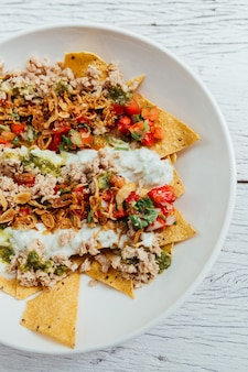 Fusion food soboro chicken nachos: japanese-style stir-fried chicken with tomato salsa