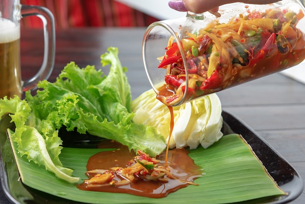 Fusion food for somtum in glass pouring on banana leaf