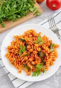 토마토 소스와 파마산 치즈에 병아리콩을 곁들인 푸실리 파스타. 건강한 채식주의 음식. 세로 샷