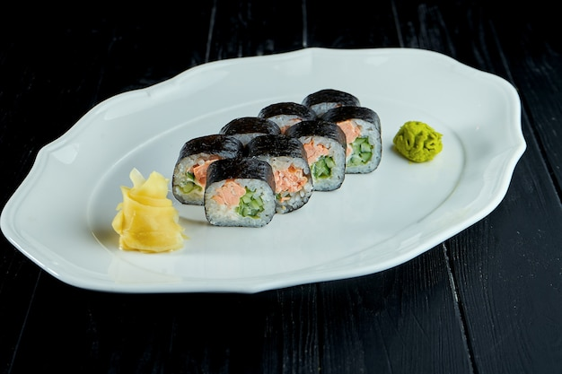 Futomak sushi roll with salmon, cucumber in a white plate on a black wooden background with ginger and wasabi.