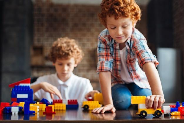 将来の自動車デザイナー。テーブルに座って遊んでいるかわいい縮れ毛の少年が運転するカラフルな造りの車に選択的に焦点を当てる