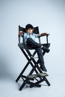 Будущий босс. довольно молодой кудрявый мальчик в повседневной одежде на белой студии
