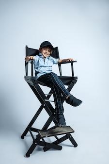 Будущий босс. довольно молодой кудрявый мальчик в повседневной одежде на белой стене. уверенно и круто. кавказский дошкольник мужского пола с яркими эмоциями на лице. детство, самовыражение, веселье.