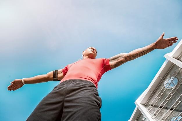 미래의 챔피언. 스포츠 챔피언이 될 준비를하는 동안 하늘을 배경으로 서있는 멋진 잘 생긴 남자