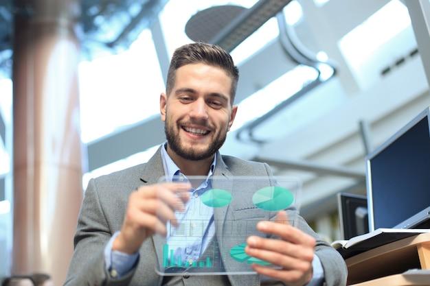 将来のコンセプト。未来的な透明なタブレット画面に表示される財務統計を分析するビジネスマン。