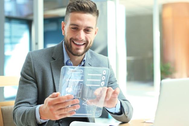 미래의 개념입니다. 미래의 투명 태블릿 화면에 표시된 재무 통계를 분석하는 사업가입니다.