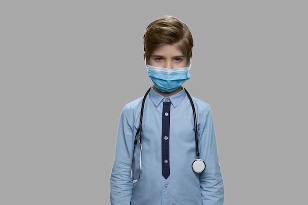 保護マスクと聴診器を持つ将来の医師。調べる準備ができている小さな医者。キッズロールプレイのコンセプト。