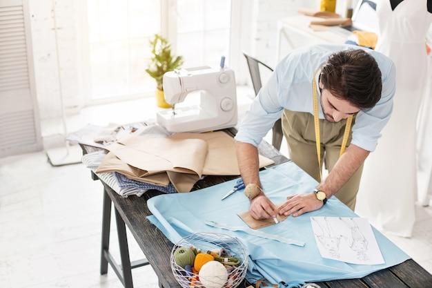 미래의 드레스. 테이블에 서서 새 드레스를 만드는 숙련 된 양장점 집중