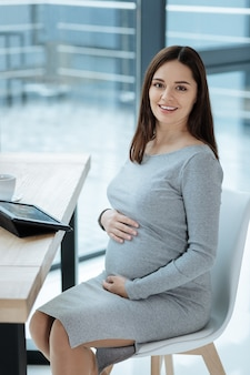 Future mother. charming pregnant woman touching her stomach with both hands while sitting on the chair and expressing optimism