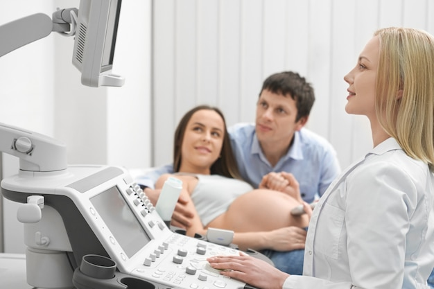 Future mother with husband on ultrasound exam in clinic.