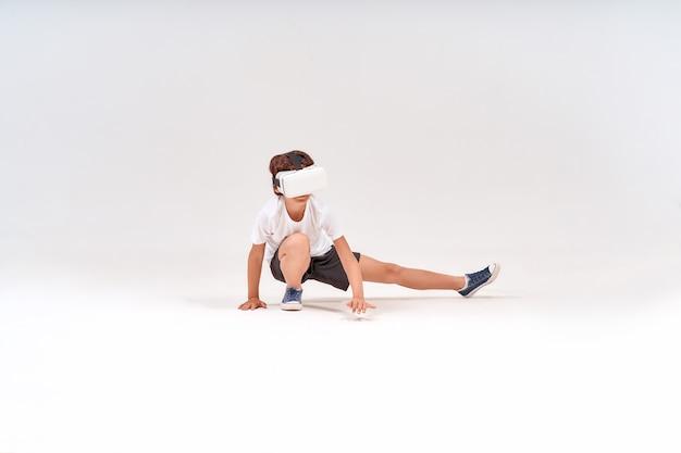 バーチャルリアリティを身に着けている10代の少年または運動しているdメガネのスポーツのフルレングスショットの未来