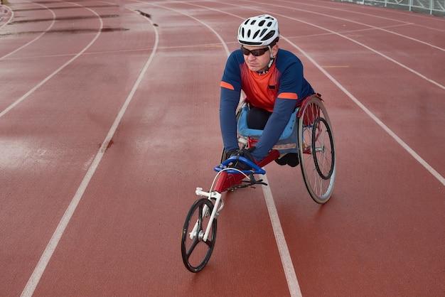 미래의 패럴림픽 챔피언. 하반신 마비 남성 운동 선수는 특수 스포츠 휠체어에 앉아 경주 전에 트랙에서 워밍업
