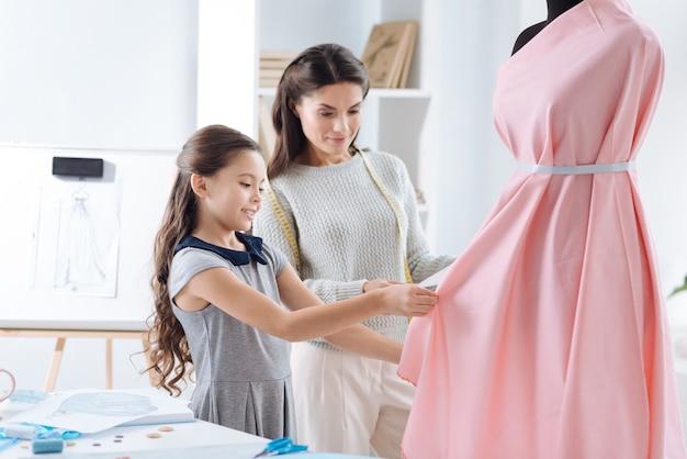 Будущая профессия. креативная милая приятная девушка стоит рядом с матерью и улыбается при разработке платья