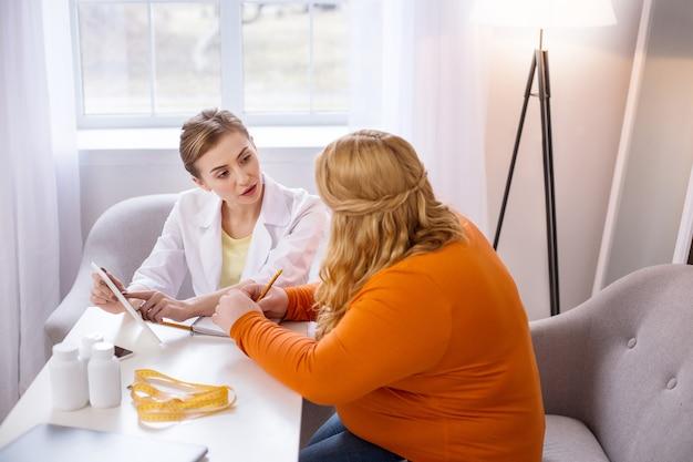 今後のステップ。太った女性と話し、彼女のタブレットを保持している決心したプロの栄養士
