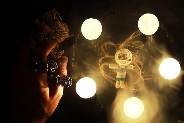 Будущий кассир. мистический натюрморт с куклой вуду, картами таро, книгами, злыми свечами и предметами колдовства. обряд гадания.
