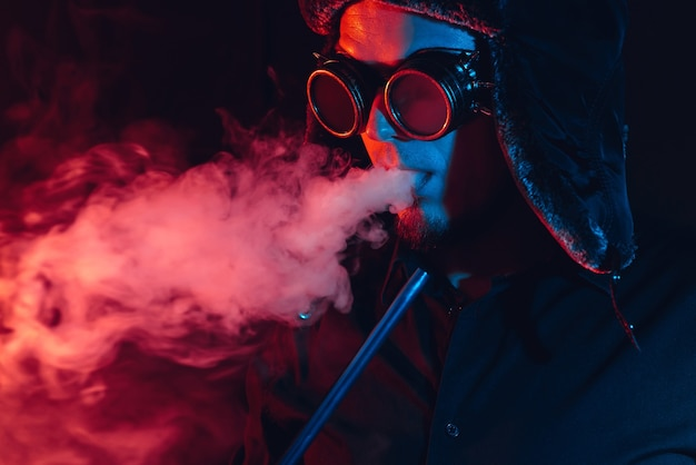 Futuristic cyberpunk portrait of a man smoking a shisha hookah and blowing a cloud of smoke with red and blue lighting