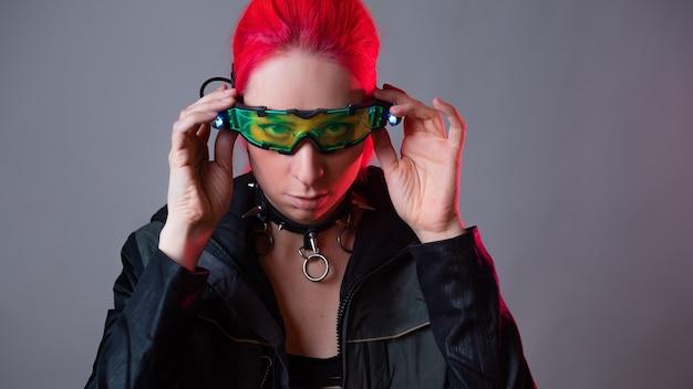 拡張現実ガジェットであるバックライト付きの未来的なメガネ。明るい眼鏡をかけたピンクの髪の若い女性、サイバーパンクのスタイルのクールな画像