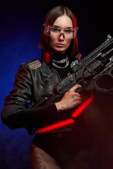 ライフルで暗い背景でポーズをとるファッショナブルなスタイルの魅力的な女性傭兵の未来的な肖像画。黒い服を着たサイバーパンクスタイルの武道の女性。