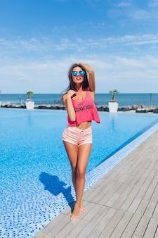 プールの近くのカメラにポーズをとって長い髪を持つ魅力的なブルネットの少女のフルレングスの写真。彼女は太陽を見ています。