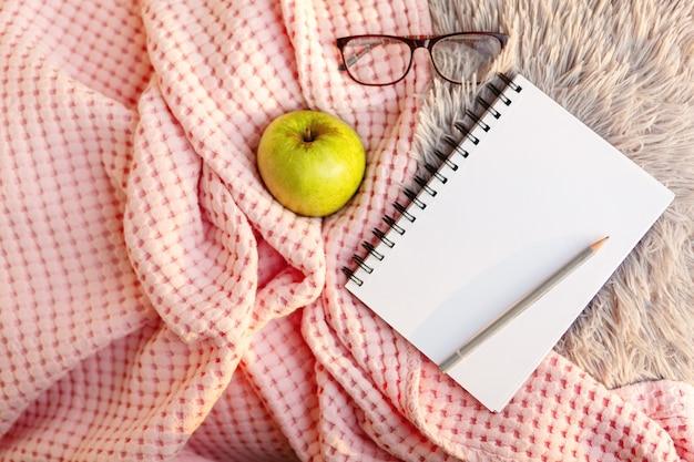 ファジーグレーのファーチェック柄とピンクのカバー、エルマ、メガネの白いノート。フラットレイ、上面図、コピースペース。居心地の良い雰囲気