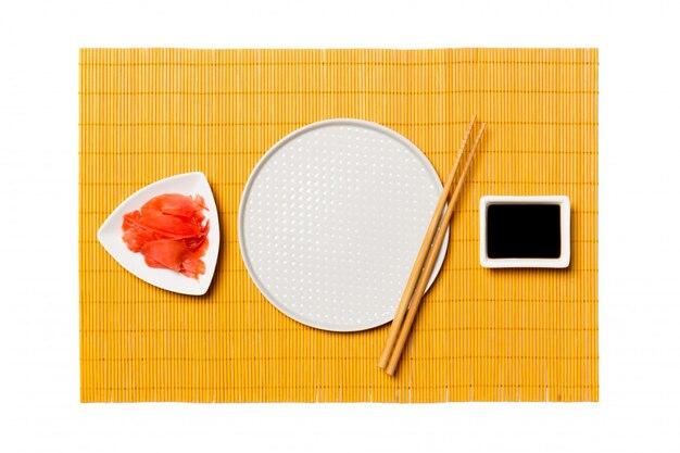 寿司と醤油、黄色の竹マットに生gの箸で空の白い丸皿。 copyspaceのトップビュー