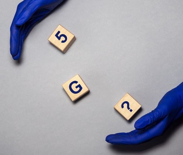 G text on wooden cubes and hands in blue protective gloves on grey table g and covid concept