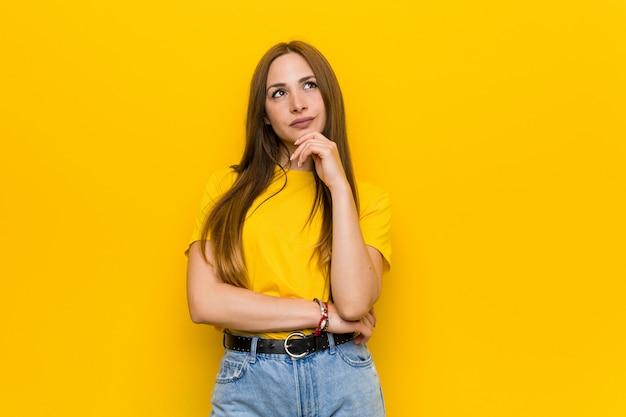 疑いと懐疑的な表情で横に探している若い生g赤毛の女性。