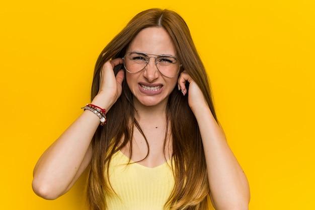 手でそばかすのない耳を覆う若い赤毛生g女性。
