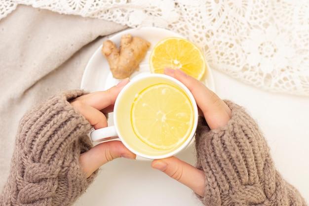 白い背景にお茶、レモン、生gと梨花の手。平干し。健康、免疫、伝統医学の概念。