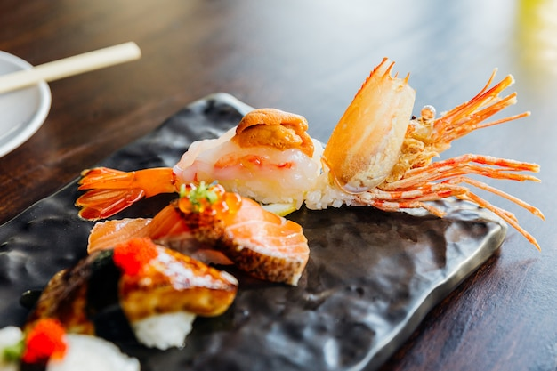 プレミアム寿司セットには、エビのフライ、フォアグラ、サーモン、えんがわのブラックストーンプレートにわさびとピンクの生gが添えられています。エビ寿司のクローズアップ。