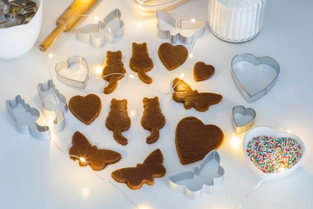 テーブルの上には生g生地の蝶、猫、ハート、クッキーを飾るための装飾、花輪が彫られています