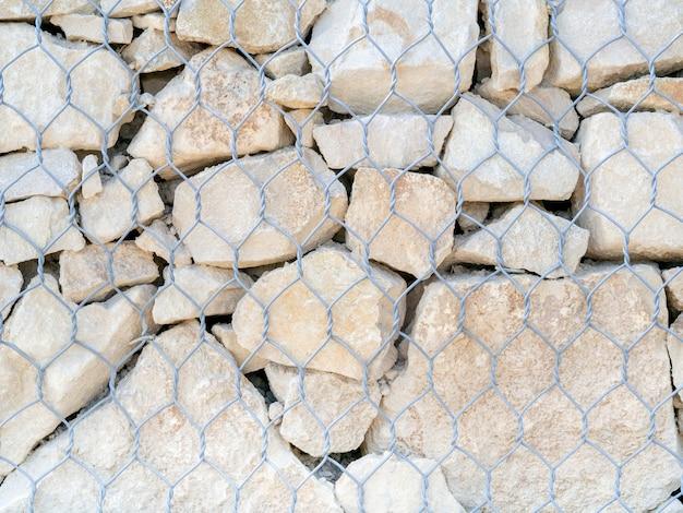 돌망태, 질감, 배경. 천연 암석과 Gabion 금속 울타리로 만든 보호 벽. 조경. 펜싱 및 테라스 프리미엄 사진