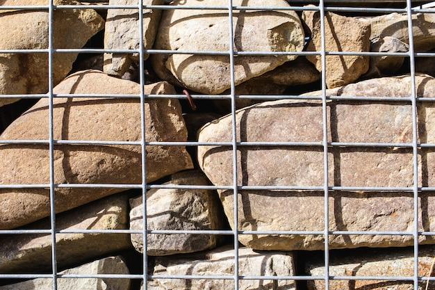 Gabion 벽 근접 촬영입니다. 질감 된 배경입니다. 침식을 방지하기 위해 사용되는 철망의 돌