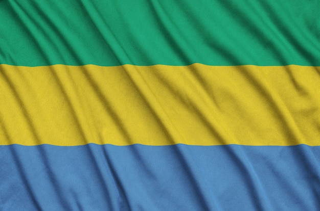 Gabon flag is depicted on a sports cloth fabric with many folds.