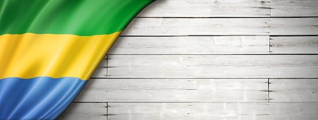 Флаг габона на старой белой стене. горизонтальный панорамный баннер.