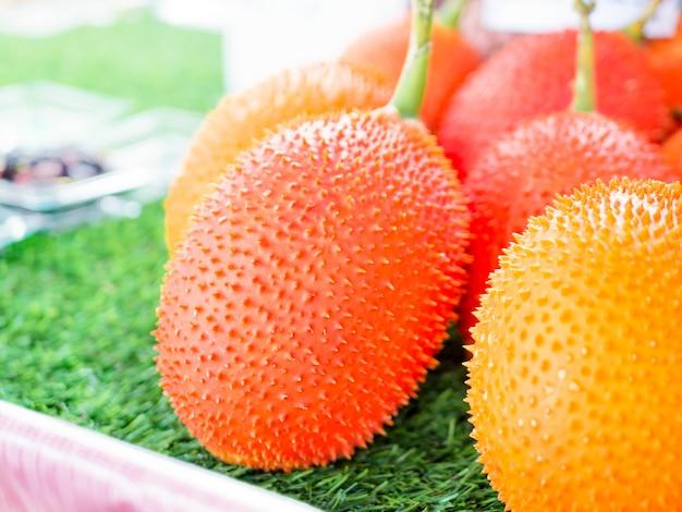 Gac фрукты, baby джекфрут, колючая горькая тыква в деревянный ящик.