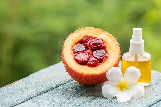 자연 배경에 gac 과일과 기름입니다.
