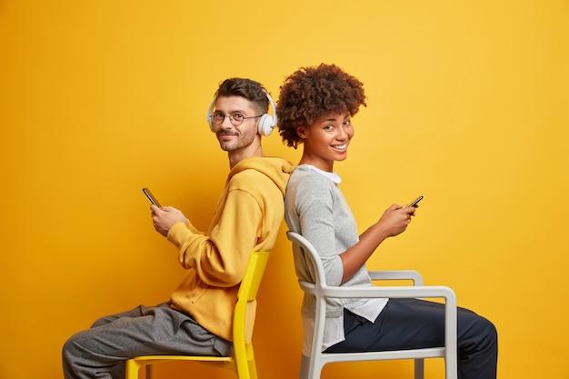 가제트 중독과 라이프 스타일 개념. 편안한 만족 된 인종 간 부부는 서로에게 다시 앉아 라이브 통신을 무시하고 현대적인 휴대 전화를 사용합니다.