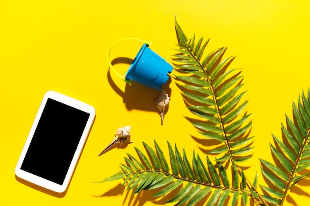 Gadget bucket and palm tree leaf on bright background