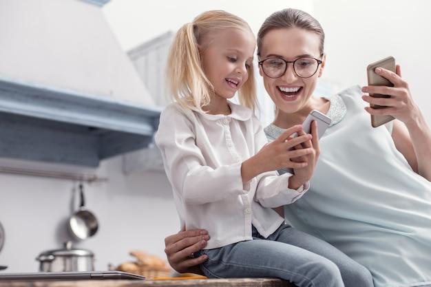 ガジェットの機能。笑いながら画面を見て、電話を持っている女の子に触発された嬉しい陽気な母と娘