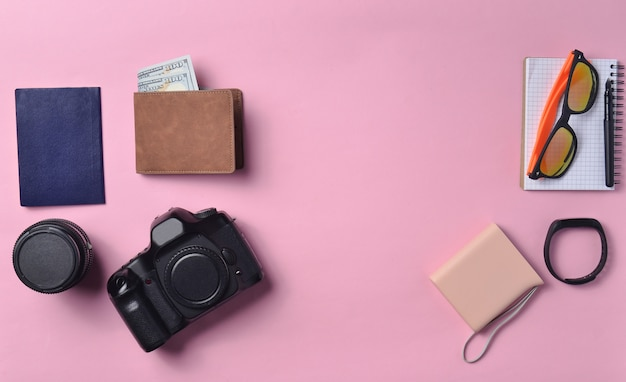 Gadgets and accessories layout on pink pastel background. photographic equipment, purse with dollars, smart clock, smartphone, notebook, sunglasses, passport, power bank.