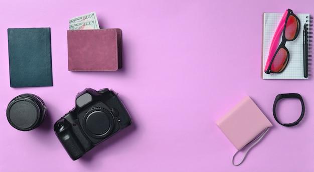 パステル調のピンクの背景のガジェットとアクセサリーのレイアウト。写真機材、ドルの財布、スマート時計、スマートフォン、ノート、サングラス、パスポート、パワーバンク