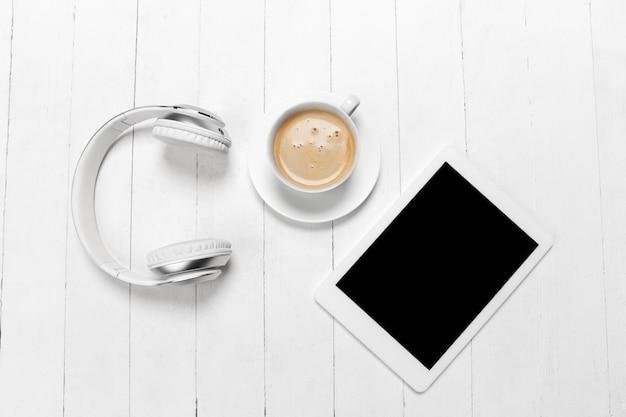 ガジェットとコーヒー。空白の画面。スタジオの壁に白い色のモノクロのスタイリッシュでトレンディな構成。上面図、フラットレイ。