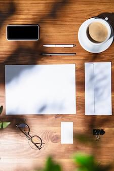 가제트, 커피, 실내 나무 테이블에 작업 도구. 홈 오피스의 창의적이고 아늑한 직장, 표면에 식물 그림자로 영감을주는 모의. 원격 사무실, 프리랜서, 분위기의 개념.