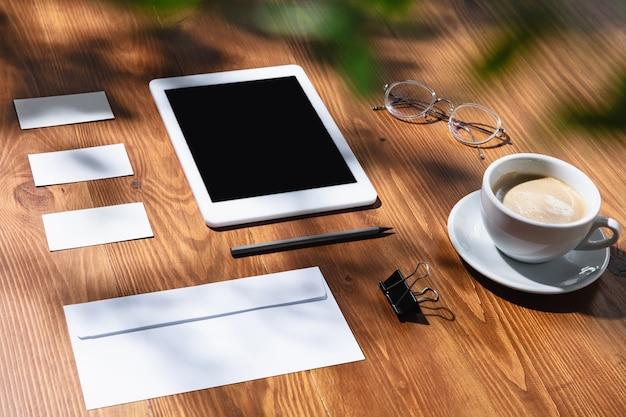 Gadget, caffè, strumenti di lavoro su un tavolo di legno per interni. luogo di lavoro creativo e accogliente in ufficio a casa, modello ispiratore con ombre di piante sulla superficie. concetto di ufficio remoto, freelance, atmosfera.